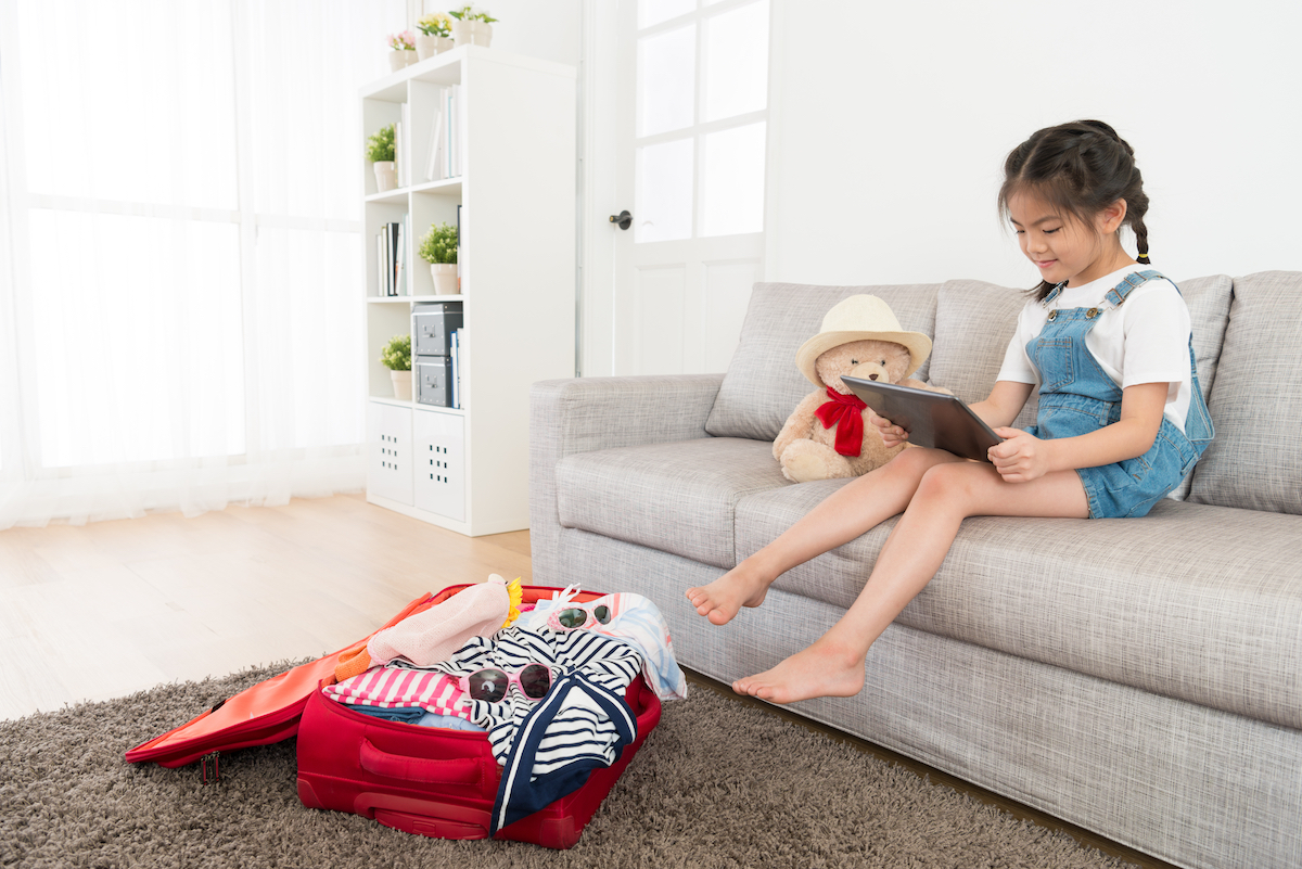 beautiful sweet kid girl sitting on living room sofa using mobile digital tablet pad searching travel information when she packing luggage suitcase at home.