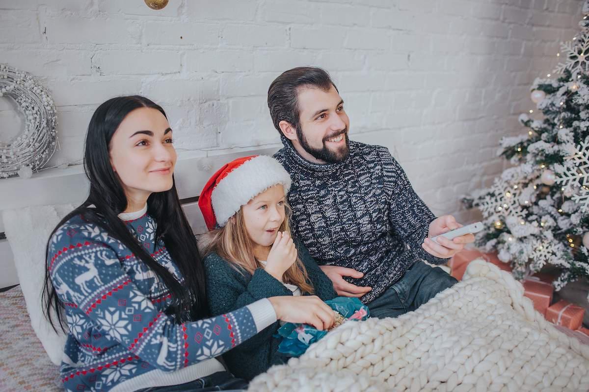 Merry Christmas and Happy New Year . Young family celebrating holiday at home. The Father is holding the remote from the TV. Dad, daughter and mother are watching television